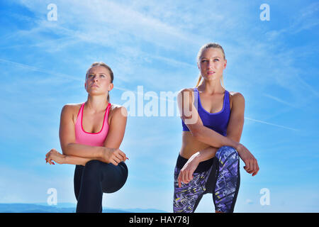 Two pretty women stretching in a park before starting a workout session - Stock Photo