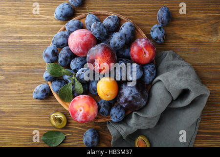 Ripe plums on rustic background, food above - Stock Photo