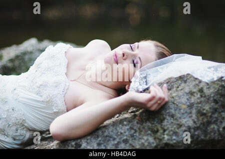 Bride lying on river rocks - Stock Photo