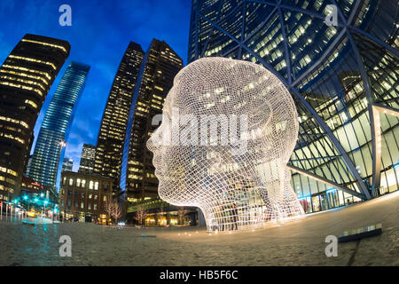 A night, fisheye view of the sculpture Wonderland by Jaume Plensa, in front of The Bow skyscraper in Calgary, Alberta, - Stock Photo