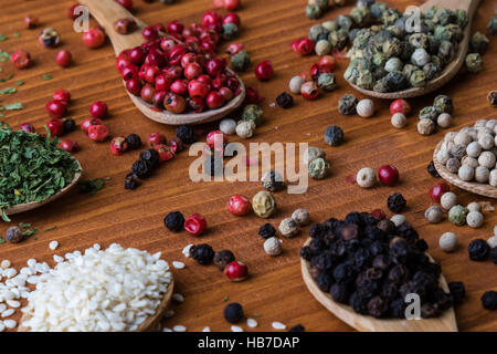 colorful spices in wooden spoons - Stock Photo