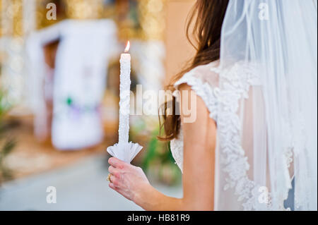 Wedding candle at hand of bride in church - Stockfoto