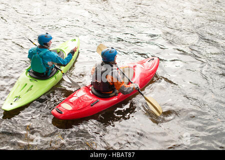 Male and female kayakers paddling on River Dee - Stock Photo
