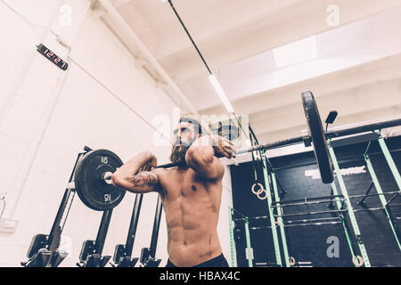 Young man weightlifting barbell in cross training gym - Stock Photo