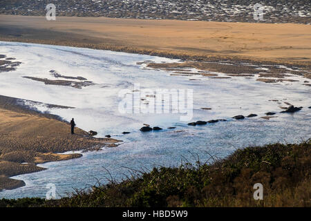 A dog walker and his dog seen in silhouette and from a distance on the award winning Crantock Beach in Newquay, - Stock Photo