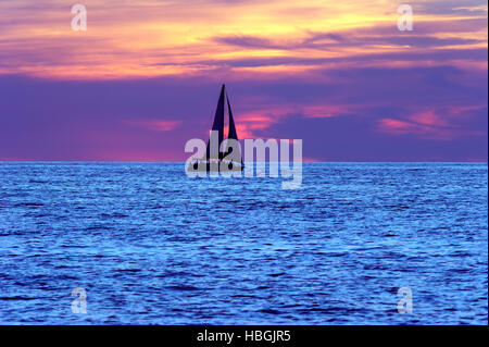 Sailboat sunset silhouette is a sailboat sailing along the water with a colorful night sky in the background. - Stockfoto