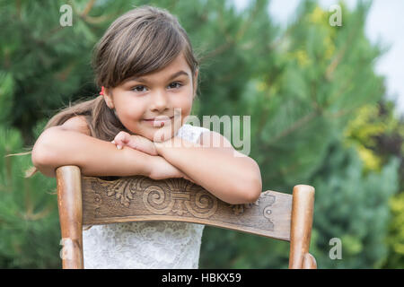 Portrait of cool long haired  brunette little girl leaning on an vintage wooden chair outdoors. - Stock Photo