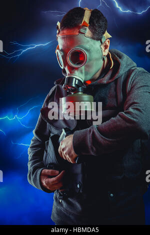Man with long leather jacket and assault rifle over storm background - Stock Photo