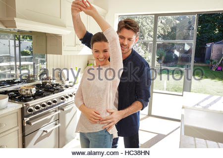 Mid adult married couple dancing together. - Stock Photo