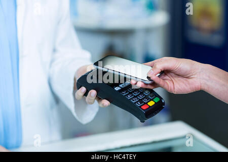 Woman paying bill through smartphone using NFC technology - Stock Photo