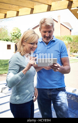 Mature Woman Looking At Design On Digital Tablet With Landscape Gardener - Stock Photo