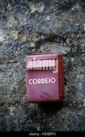 Red mail box on stone wall. Portugal - Stockfoto