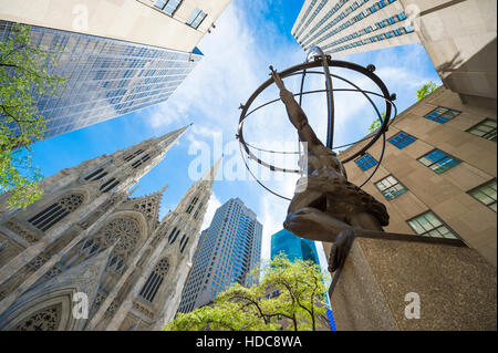 NEW YORK CITY - SEPTEMBER 3, 2016: The statue of Atlas in Rockefeller Center stands across from St Patrick's Cathedral. - Stock Photo