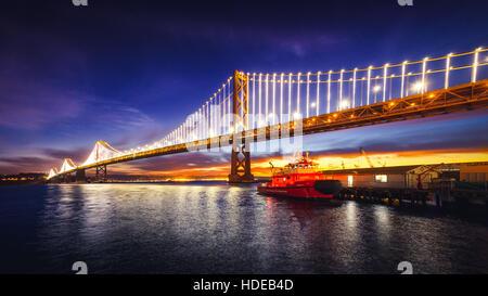 San Francisco Oakland Bay Bridge Illuminated at Sunrise, California - Stock Photo