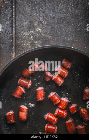 Fried smoked  sausages in the pan on the metal background vertical - Stock Photo