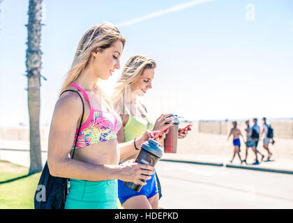 Two women looking at cellular phone outdoors - Two pretty girlfriends having fun with modern technology devices - Stockfoto