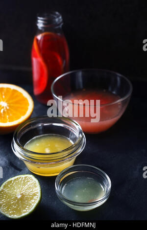 Citrus juice in the different glass bowl on the dark stone background - Stock Photo