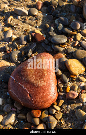 Heart shaped stone on the beach. Vertical image. - Stock Photo