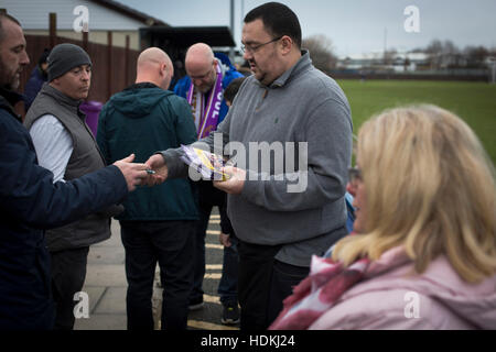 A spectator buying a match programme at the Delta Taxis Stadium, Bootle, Merseyside before City of Liverpool hosted - Stock Photo