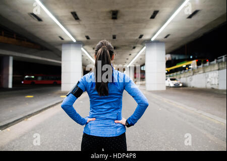 Young runner under the bridge in the evening, resting - Stock Photo