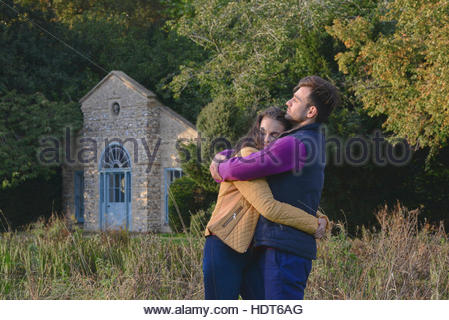 Young couple hugging beside stone building. - Stock Photo