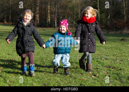 Three sisters: girls age 4, 2 & 6 years, four, two, and six year old, running run play in grass park / parkland - Stock Photo