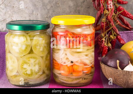 pickeled vegetables in a jar with onions and dried peppers - Stock Photo