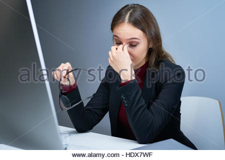 Portrait of exhausted woman at office desk in front of computer screen taking glasses off and rubbing her nose bridge - Stockfoto