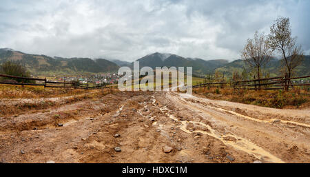 Muddy ground after rain in Carpathian mountains. Extreme path rural dirt road in the hills - Stock Photo
