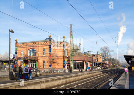 Uelzen, Germany - December 04, 2016: People waiting on the platform at the train station designed by Austrian artist - Stock Photo