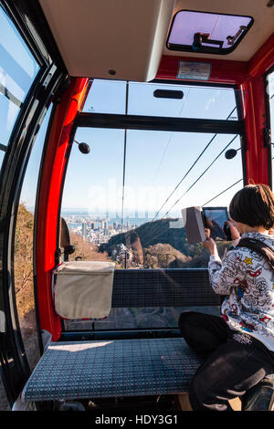 Japan, Kobe. Caucasian child, young male teenager, in cable car on Shin-ropeway, using ipad to film the route and - Stock Photo