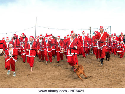Perranporth, Cornwall, UK. 18th December 2016. Santa's on the sand an annual charity run on Perranporth beach in - Stock Photo