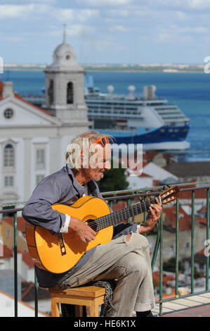 Busker busking playing guitar Lisbon Portugal - Stock Photo