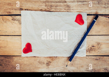 old paper and red heart with pencil on wood background for valentine greeting card. - Stock Photo