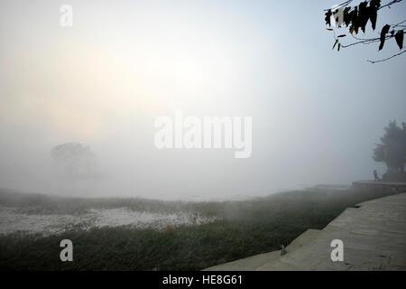 Kathmandu, Nepal. 18th Dec, 2016. A girl exercising on a misty morning as the sun rises over at the Taudaha Wetland - Stock Photo