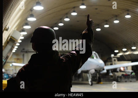 A crew chief signals to a pilot prior to taxiing in support of a simulated combat sortie in support of exercise - Stock Photo