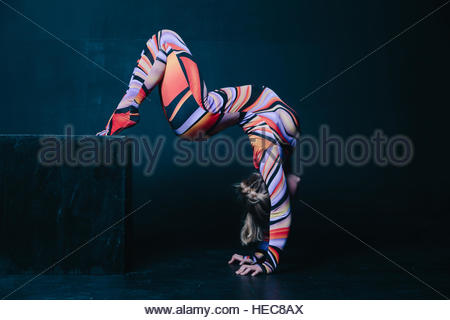 Young flexible blonde circus acrobat posing in studio in costume. Doing equilibre balance handstand on a cube. Copy - Stockfoto