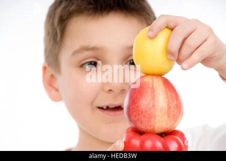 7-year-old boy stacking a pepper, an apple and a lemon - Stock Photo