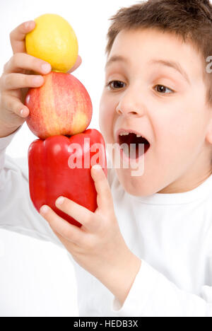 7-year-old boy holding a pepper, an apple and a lemon - Stock Photo