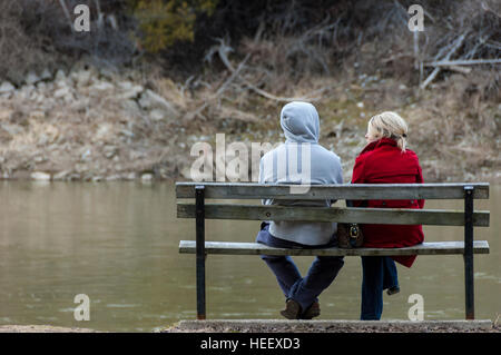 A young couple sitting on a park bench in the Fall with their backs to the camera. - Stockfoto