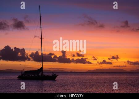beautiful sea sunset in Whitsunday Australia, with blood red sky and a boat silhouette - Stock Photo