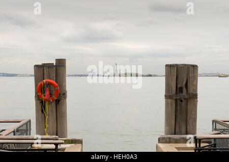 Statue of Liberty at the horizon seen from Battery park in lower Manhattan - Stock Photo