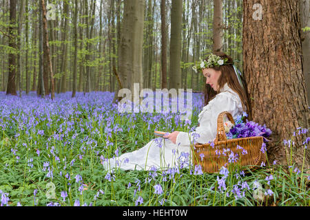 Victorian woman in white dress in a springtime bluebells forest - Stock Photo