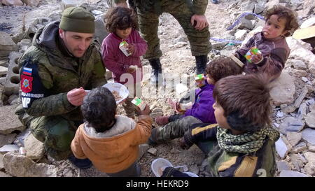 Aleppo, Syria. 23rd Dec, 2016. A serviceman feeds kids in the neighborhood of Karm al-Miasar in the eastern part - Stockfoto
