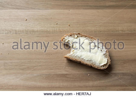 A bitten into slice of bread with butter - Stock Photo