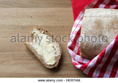 Loaf of Organic Full Oat Bread on a Wooden Board  with red and white kitchen Towels - Stockfoto