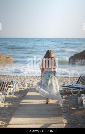 Young woman walking along wooden boardwalk towards the beach - Stock Photo