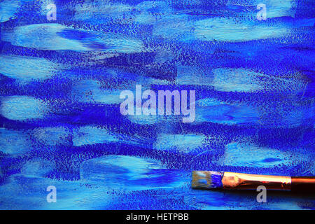 Closeup of the brush on blue painting background - Stock Photo