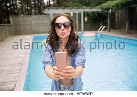 Woman taking selfie with mobile phone beside swimming pool, Amagansett, New York, USA - Stock Photo