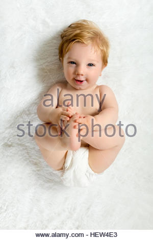 Toddler lying on blanket, holding feet, smiling - Stock Photo